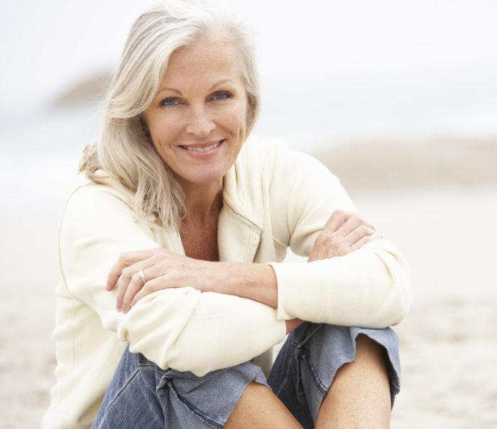 Senior Woman On Holiday Sitting On Winter Beach