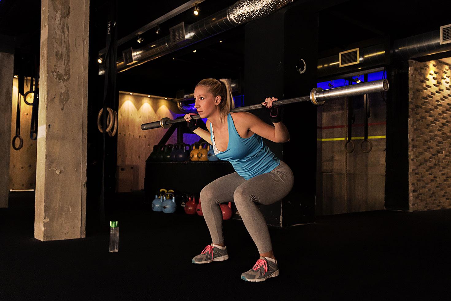 Тренировка на заднюю поверхность бедра девушки в тренажерном