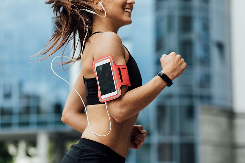 Девушка со смартфоном занимается фитнесом